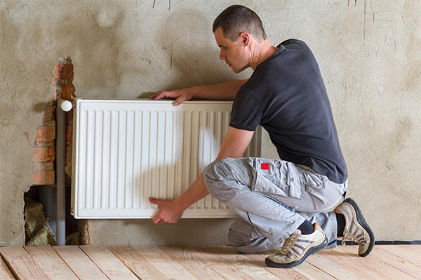 Photo d'un artisan en train de mettre en place un chauffage